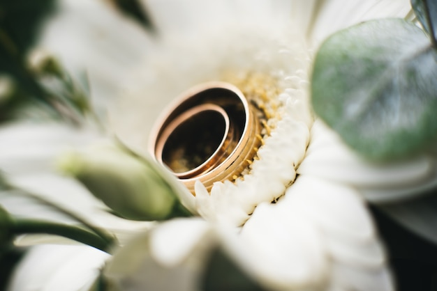 Wedding engagement rings and flowers wedding bouquet, selective focus, macro