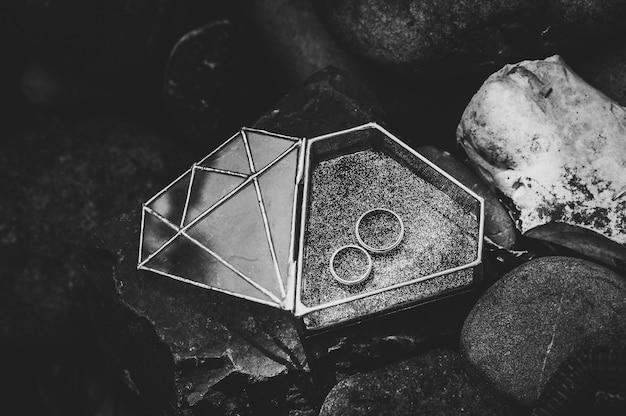 Обручальные кольца для помолвки в металлической стеклянной шкатулке в форме ромба.
