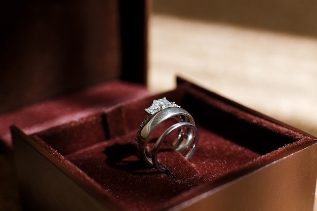 Wedding and engagement rings shining in brown box