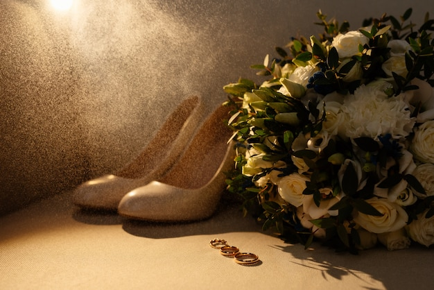Wedding and engagement rings with a wedding bouquet, bride's shoes