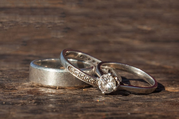 Wedding and engagement rings on woden background
