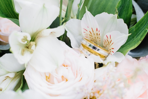 Wedding engagement rings of yellow and white gold are on the wedding bouquet
