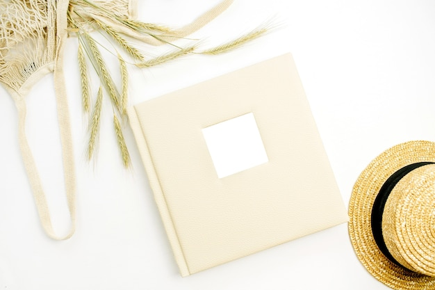 Wedding or family photo album, rye ears in string bag, straw hat on white surface
