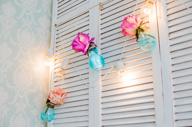 Wedding floral decoration in the form of mini-vases and bouquets of flowers hanging from the ceiling.  light bulb decor. cozy modern stylish room