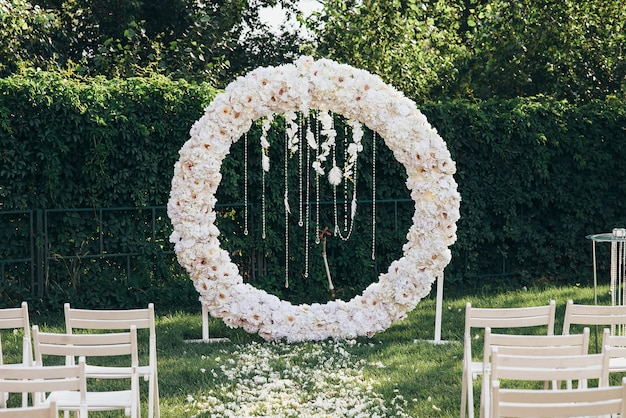 Wedding flower arch in white round shape with beads and feathers next to white wooden chairs in nature