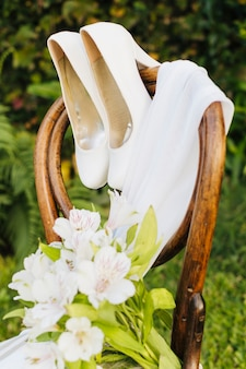 Wedding flower bouquet; high heels and scarf on wooden chair in the park
