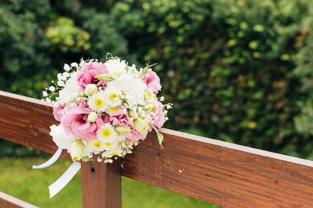 Wedding flower bouquet tied on wooden railing in the park