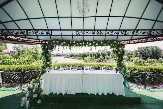 自然の緑の背景にキャンドルと結婚式の花のテーブルの装飾。