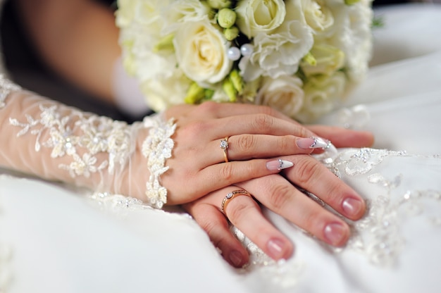 Wedding flowers bouquet in bride hands with white dress