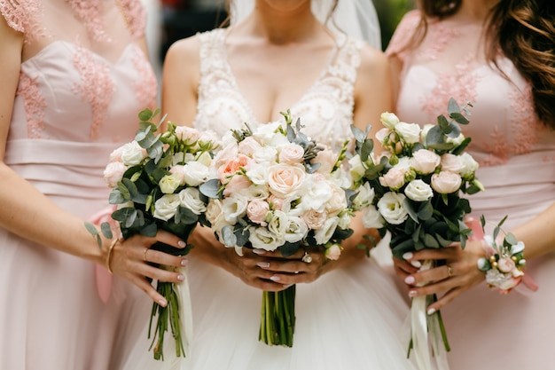 Wedding flowers, bride and bridesmaids holding their bouquets at wedding day