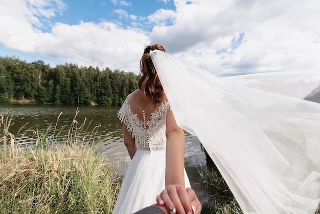 Wedding follow me concept. the bride holds the hand of the groom on the wedding day in the summer in nature by the river Premium Photo