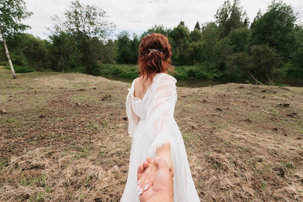 Wedding follow me concept. bride holds and leads the groom on the wedding day in the summer in nature
