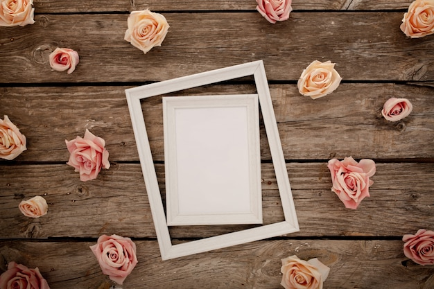 Wedding frame with pink roses on brown wooden background.