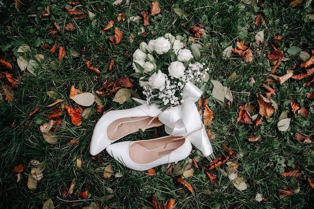 공원의 푸른 잔디에 있는 흰색과 분홍색 장미와 굽 높은 신발의 부드러운 웨딩 부케