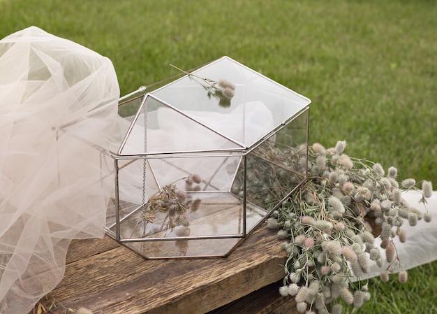 Свадебная стеклянная шкатулка для конвертов для поздравлений на деревянном столике и белая ткань с растениями в качестве украшения.