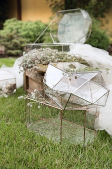 Wedding glass boxes for envelopes for greetings on little wooden table and the  white tissue with plants as a decoration