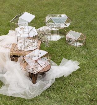 Свадебные стеклянные коробки для конвертов для поздравлений на деревянном столике и белая ткань с растениями в качестве украшения.
