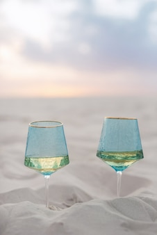 Wedding glasses made of blue glass buried in the sand of the beach