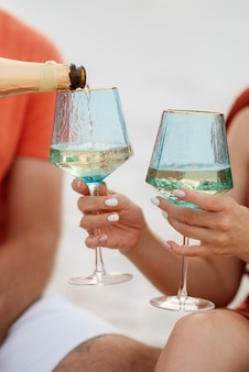 Wedding glasses made of blue glass with champagne in hand