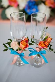 Свадебные бокалы на столе с украшениями и цветами