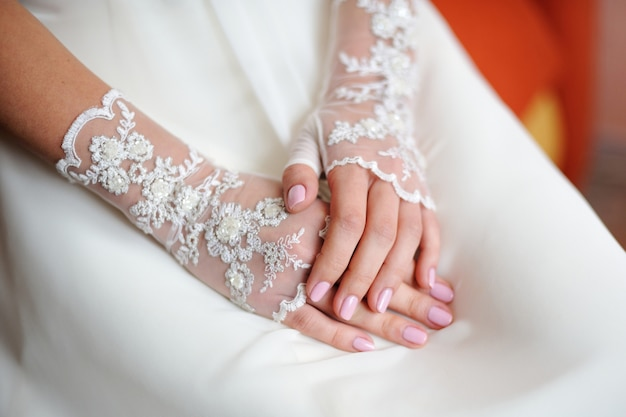 Wedding gloves on the hands of the bride