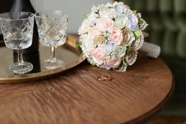 결혼 금 반지와 가벼운 웨딩 부케.