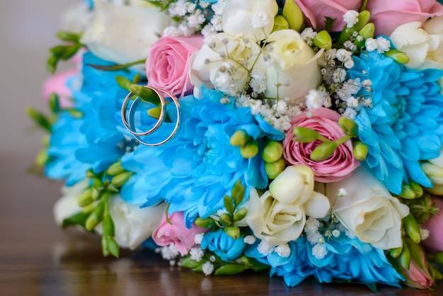 결혼 금 반지와 나무 테이블에 파란색, 흰색, 분홍색 꽃의 웨딩 부케