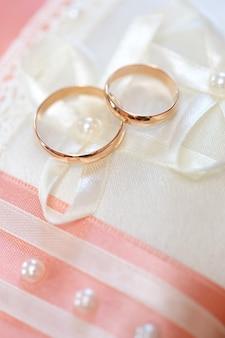 Обручальные золотые кольца жениха и невесты на декоративной подушке.
