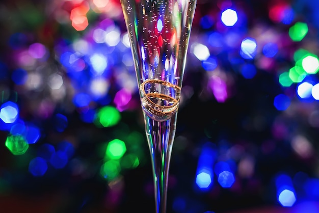 Wedding gold rings in a glass of champagne on a bright colorful