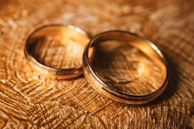 Wedding gold rings lie on background covered with strokes of oil brown-gold paint.
