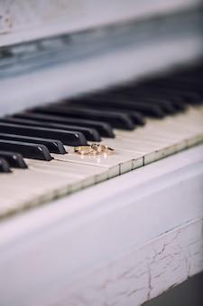 피아노의 흰색 키에 결혼 금 반지. 의식, 종교, 음악, 빈티지, 관습, 장식.