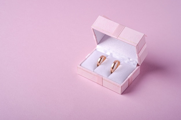 Wedding gold rings in pink gift box on soft pink background, angle view, copy space