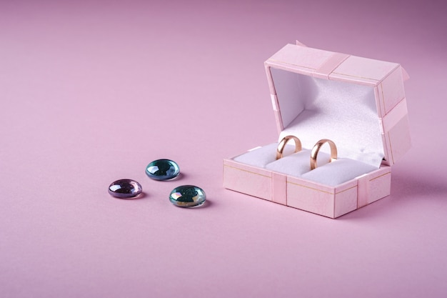 Wedding gold rings in pink gift box with glass marbles on soft pink background, angle view, copy space