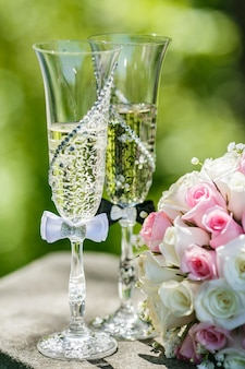Wedding gold rings with roses and glasses of champagne