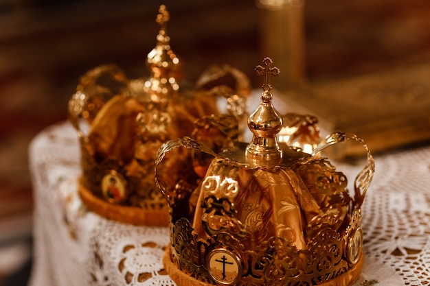 Wedding golden crowns on the table in church. wedding crowns in church ready for marriage ceremony.