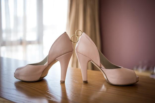 花嫁のピンクの靴の間の結婚式の金の指輪。式