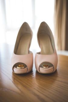 花嫁のピンクの靴の中の結婚式の金の指輪。式。垂直