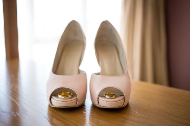 花嫁のピンクの靴の中の結婚式の金の指輪。式