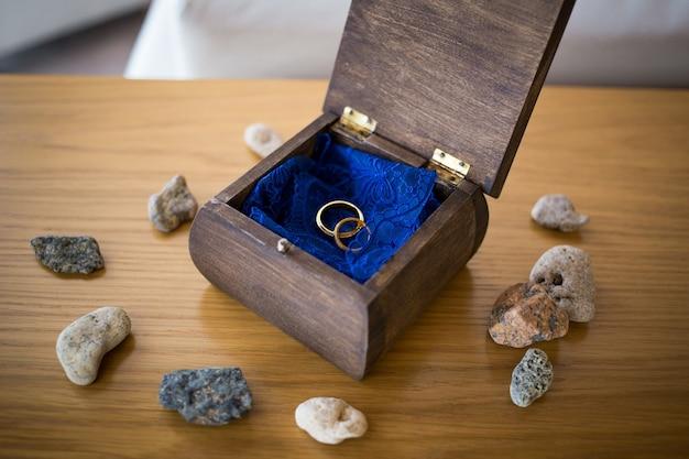 주위에 돌을 가진 열린 나무 상자 안에 황금 반지를 결혼. 의식