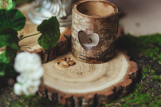 Свадебные золотые кольца на пне в зеленой траве