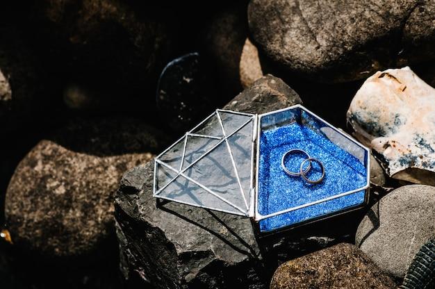 金色の銀の婚約指輪をガラスの金属製の箱で結婚式。