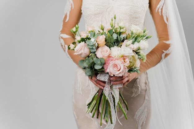 Свадебный зеленый букет с эвкалиптом, розами, пионами в руках женщины в студии на белой глухой стене. крупный план букета реклама для флориста.