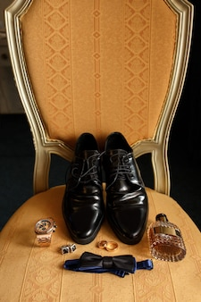 Wedding groom accessories on chair: black shoes, wrist watch, perfume bottle, bow tie near wedding rings