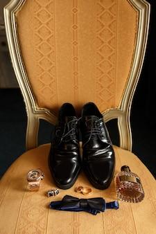 Свадебные аксессуары для жениха на стуле: черные туфли, наручные часы, флакон духов, галстук-бабочка возле обручальных колец