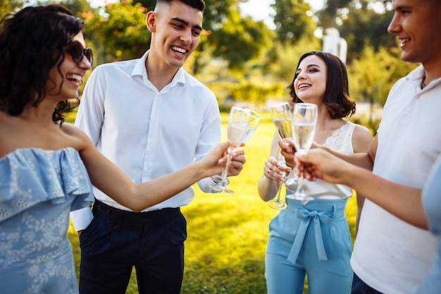 Wedding guests clinking glasses.  guests toasting and cheering at stylish celebration.