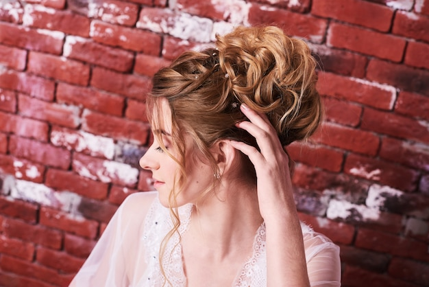 Wedding hairstyle for beautiful bride on loft wall