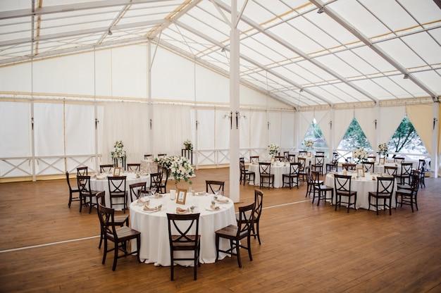 Свадьба в палатке. украшение зала. белые скатерти, красивый декор и посуда.