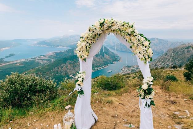 式典のための山の結婚式のアーチでの結婚式