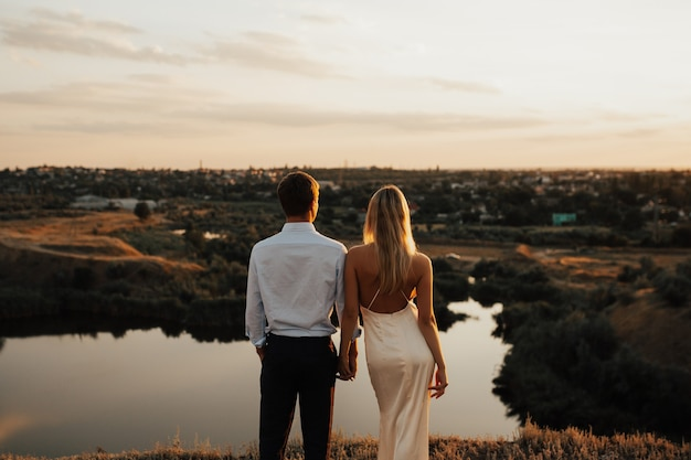 川のある山での結婚式。新郎は花嫁の手を優しく握ります。