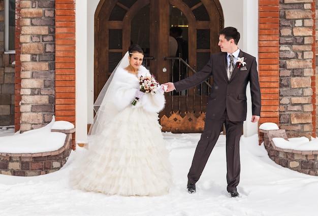冬の結婚式。雪に覆われた公園の新婚夫婦